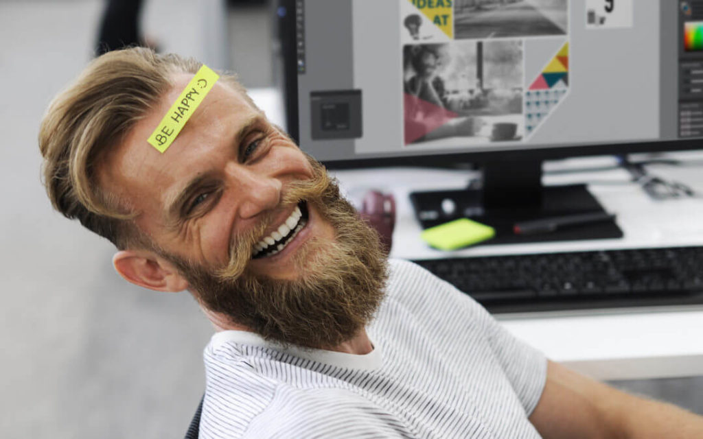 "Happy, smiling man with a beard and a sticker on his head that says ""Be happy"""