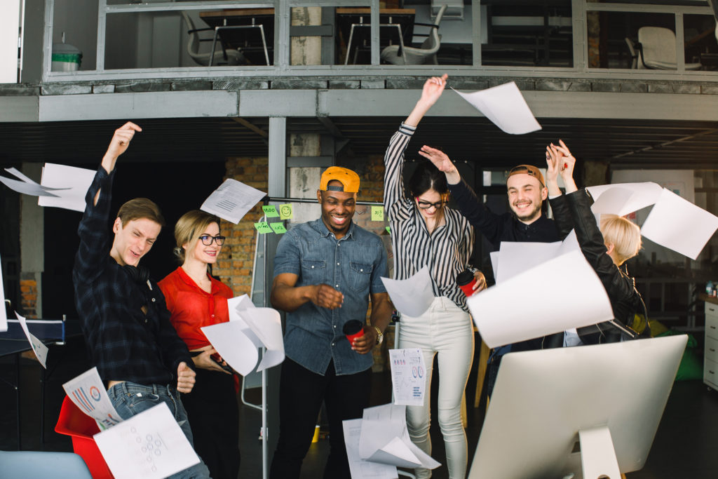 Photo of a group of marketing and salespeople throwing papers up into the air