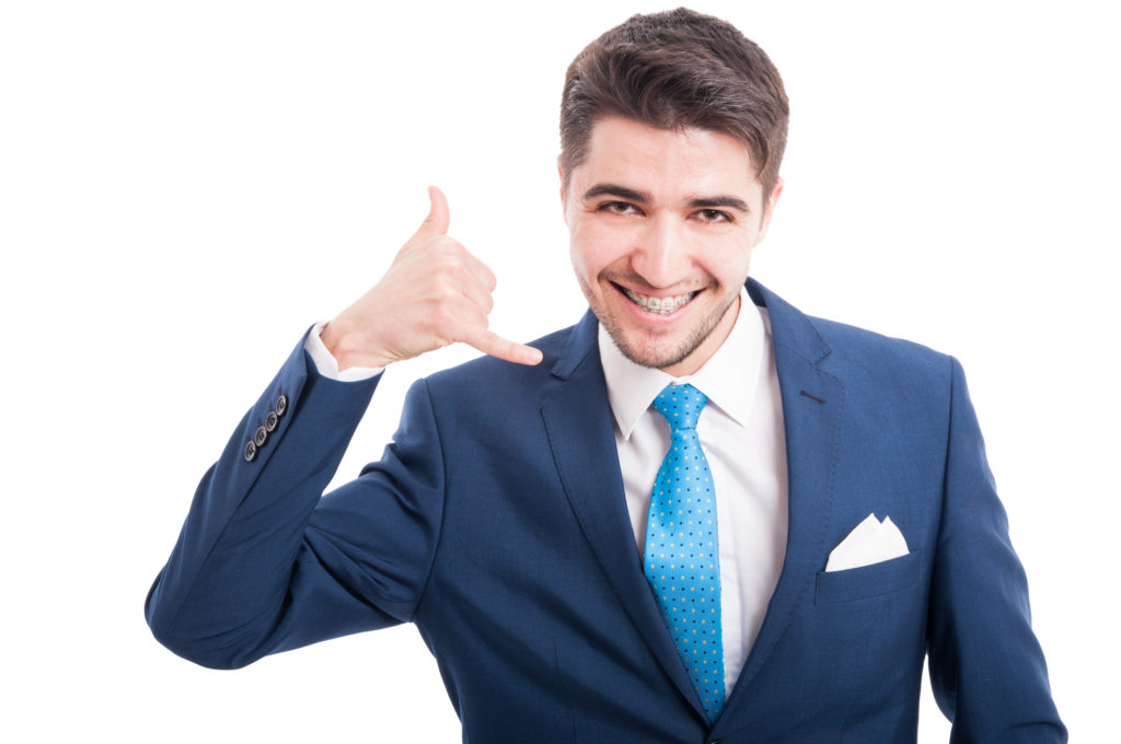 """Cheesy image of man with braces holding his hand up in a """"phone"""" formation next to his head"""
