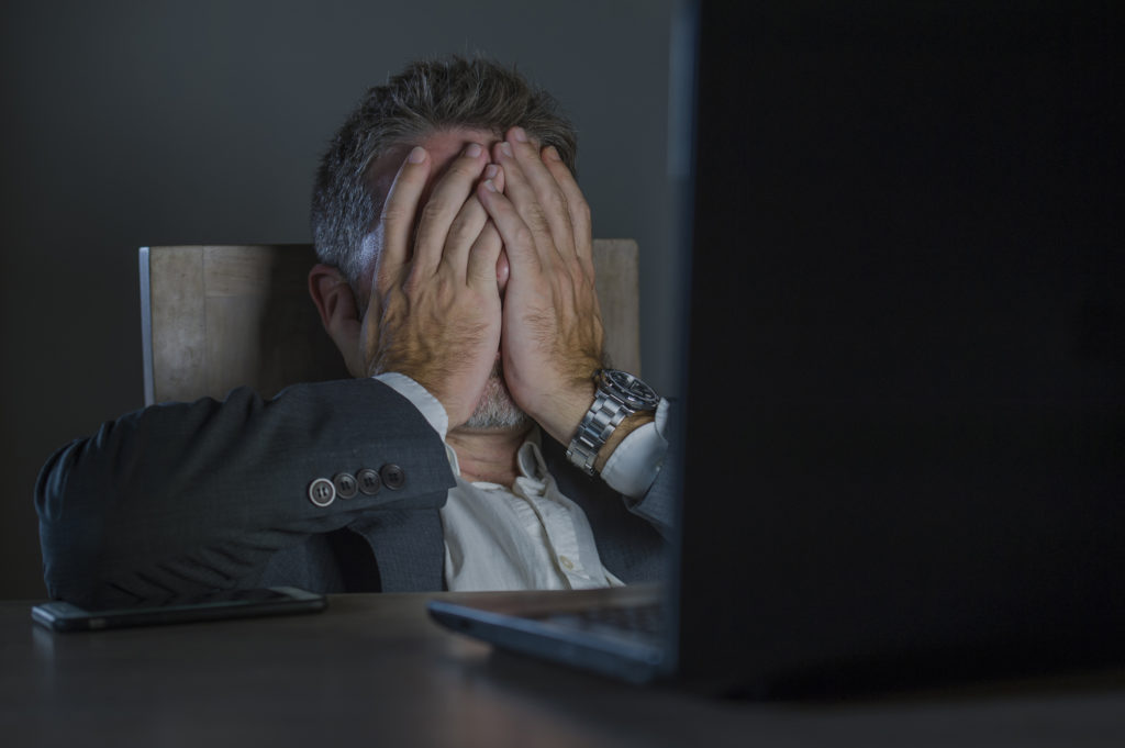 Man in front of computer with hands over his face