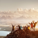 happy people climbing mountain in the sunset