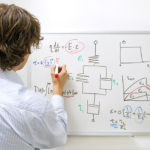 An engineer drawing a complexe physics equation on a whiteboard